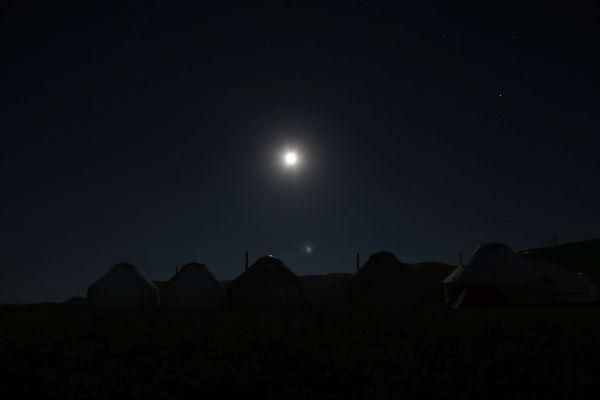 sehr dunkel, oben mittig der Mond, unten sind als Schattenriss Jurten zu erkennen